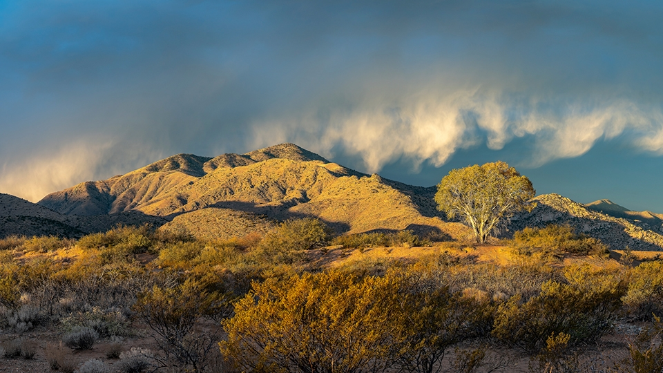 """Storm clouds """"dance"""" over rugged mountains in a view from Apache Pass Road. 